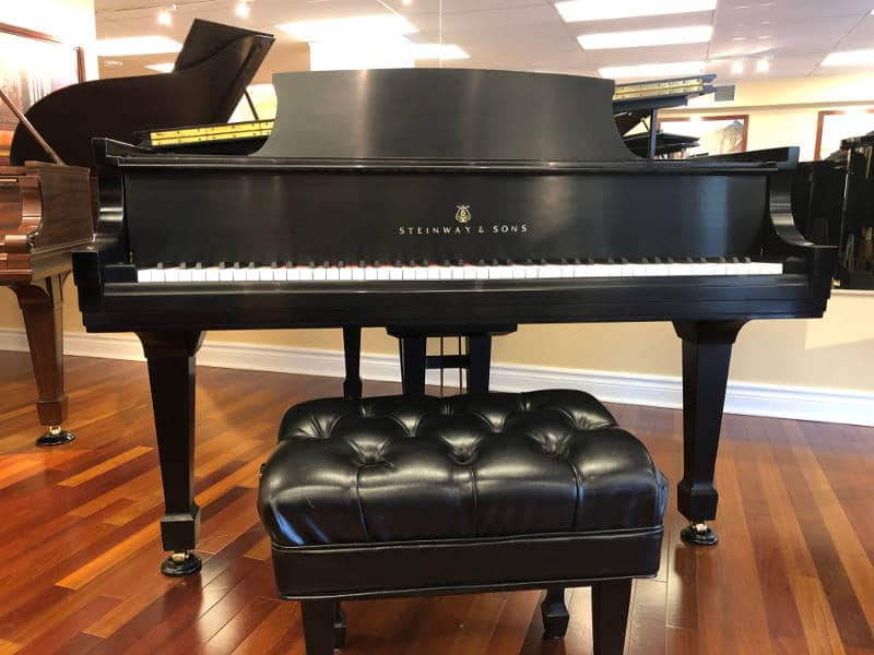 """1983, 5'7"""" model M Steinway grand piano & matching adjustable concert artist bench in satin ebony finish, serial #479036."""